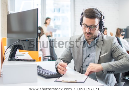A young man sits at a table in the office, holds a pen in his hand and works with a computer and doc Stock photo © Traimak