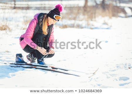 Woman cross country skier putting on ski Stock photo © Kzenon