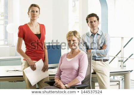 Business team standing in cubicle smiling Stock photo © monkey_business