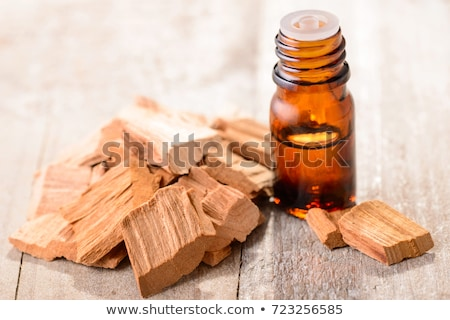 a bottle of sandalwood essential oil with sandalwood pieces stock photo © madeleine_steinbach