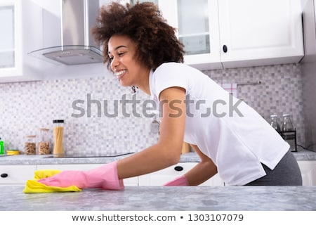 African Woman Cleaning Kitchen Counter Stock photo © AndreyPopov