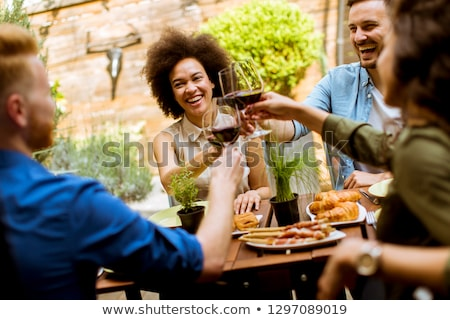 Cheerful young people have lunch in the courtyard and toasting w Stock photo © boggy