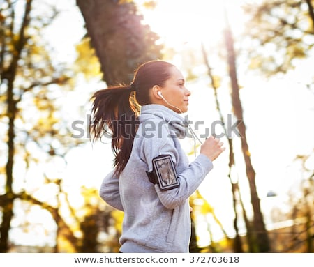 woman with earphones running at park Stock photo © dolgachov