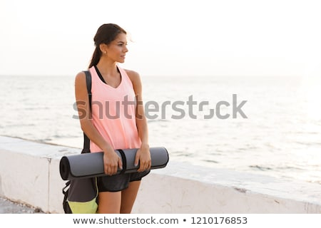 Smiling young sportswoman holding fitness mat Stock photo © deandrobot