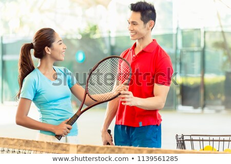 Tennis instructor teaching the correct grip for holding the racket Stock photo © Kzenon