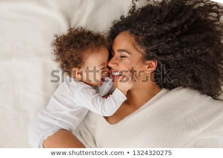 Mother and baby girl on a white bed Stock photo © Lopolo
