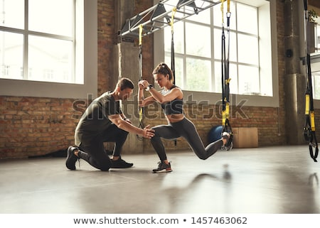 fitness couple in sportswear doing squat exercises at gym stock photo © andreypopov