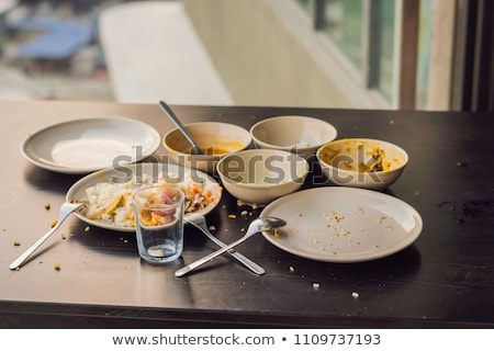 the remains of food in plates crumbs on the table after lunch or dinner vertical format for instagr stock photo © galitskaya