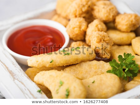 Buttered chicken nuggets and popcorn bites in vintage wooden box with ketchup and glass of cola on w Stock photo © DenisMArt