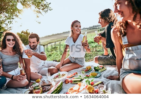 Stock photo: Diverse group of friends enjoying a beer in the park