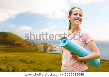 happy smiling woman with exercise mat over big sur Stock photo © dolgachov