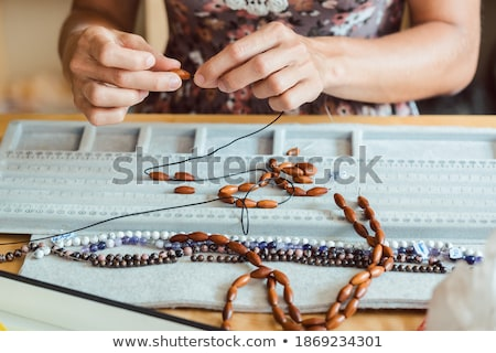 Close-up of woman making a necklace from gemstones Stock photo © Kzenon
