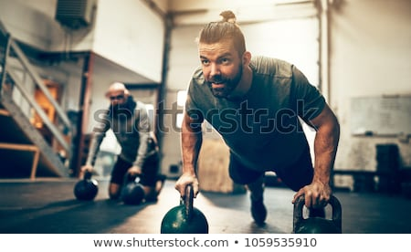 Image of young athletic man doing exercise while working out Stock photo © deandrobot