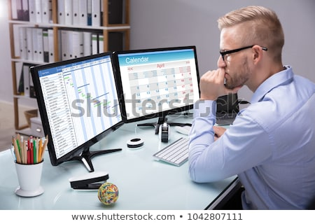 Harmonogram ekranie komputera pracownika patrząc kalendarza komputera Zdjęcia stock © AndreyPopov