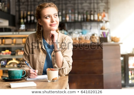 young woman sitting at a table with cappuccino coffee making puss face Stock photo © Rob_Stark