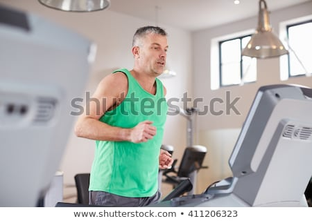 Middle-aged man working out on a treadmill Stock photo © d13