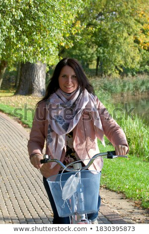 girl riding vintage bike on fall season at park stock photo © cienpies