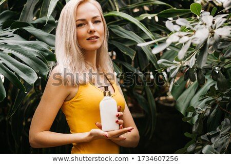 Attractive woman in swimsuit standing and holding bottle of soda Stock photo © deandrobot