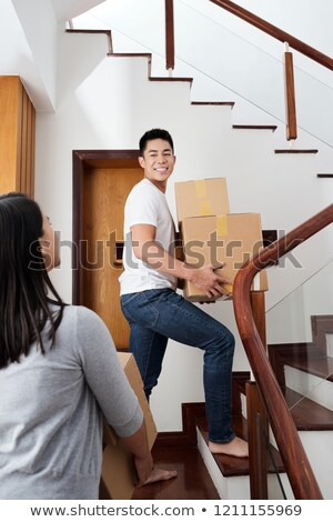 happy young woman carrying a box upstairs stock photo © dash