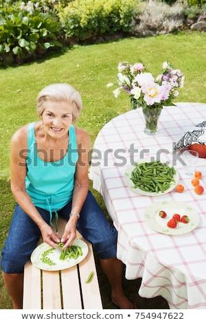 Mature woman peeling pods in garden. Stock photo © IS2