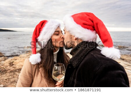 Portrait of lovers kissing at sunset and holding glass with wine at home Stock photo © deandrobot
