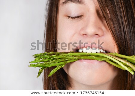 Young girl holding bunch of asparagus and smiling Stock photo © monkey_business