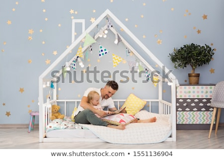 Stock photo: father and baby daughter with book at home