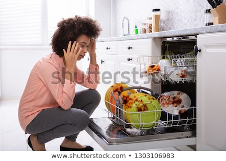 worried woman looking at the dirty plates in the dishwasher stock photo © andreypopov