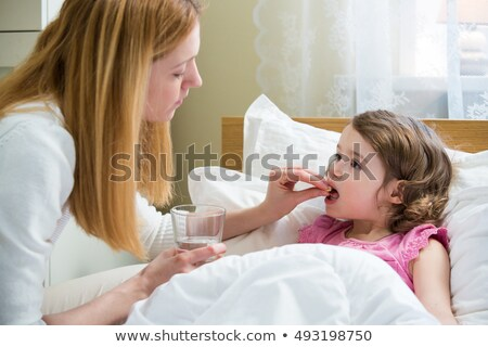 girl lying on bed taking medicine stock photo © andreypopov