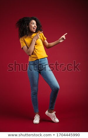 full length photo of positive woman 20s with curly hair pointing stock photo © deandrobot