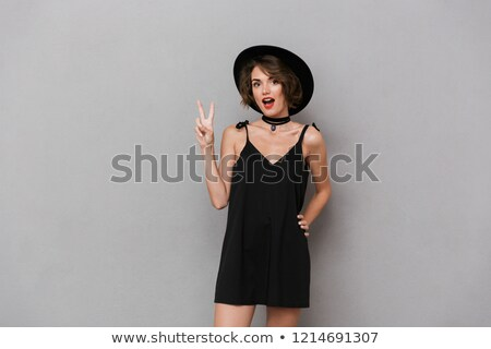 photo of kind woman 20s wearing black dress and hat smiling at c stock photo © deandrobot