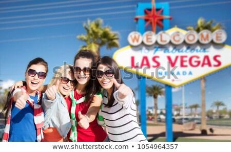 happy teenage girls showing thumbs up at las vegas Stock photo © dolgachov