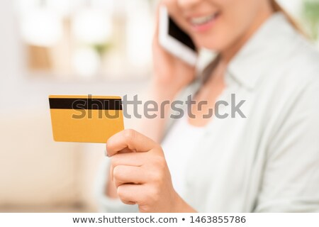 Yellow plastic card with black magnet line in hand of young female consumer Stock photo © pressmaster