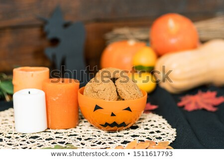 halloween plastic bowl with cookies and three candles on white knitted napkin stock photo © pressmaster