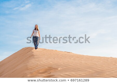 young woman in rad sandy desert at sunset stock photo © galitskaya