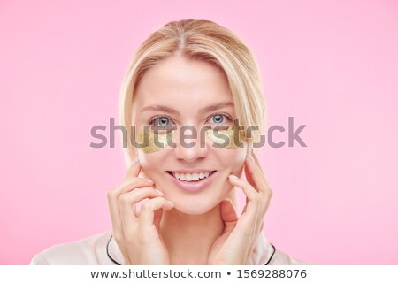 Smiling blond girl with golden revitalising under-eye patches touching her face Stock photo © pressmaster