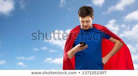 man in red superhero cape with smartphone over sky Stock photo © dolgachov