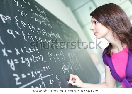 pretty young college student writing on the chalkboard stock photo © lightpoet