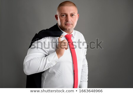 Girl in red holding businessman by his tie Stock photo © stockyimages