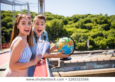 joyful couple holding globe and smiling at camera stock photo © stockyimages