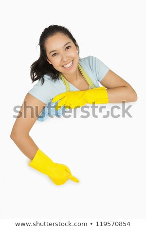 Smiling woman in apron and rubber gloves leaning on white surface with a rag Stock photo © wavebreak_media