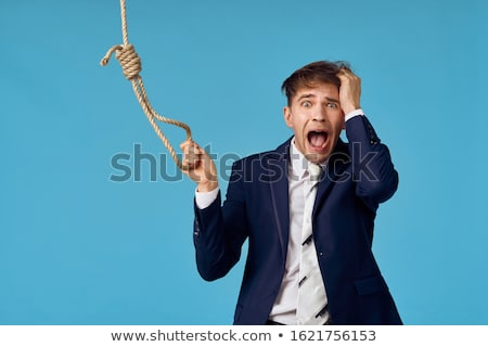 Foto d'archivio: Man In Suit Holding A Rope With A Hangmans Noose