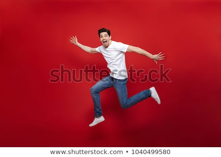 Сток-фото: Casual Young Man Jumping Over White Background
