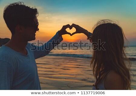 Cuore simbolo tramonto mani adolescenti silhouette Foto d'archivio © rafalstachura