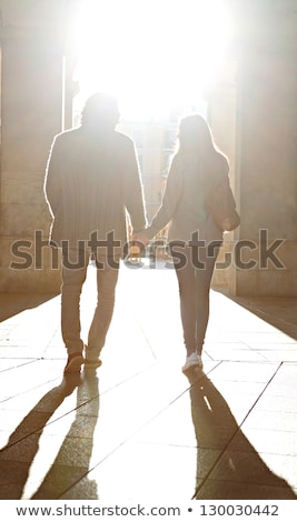 Silhouette Of Couple Walking While Holding Hands stock photo © HdcPhoto