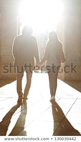 Silhouet paar lopen holding handen water liefde Stockfoto © HdcPhoto