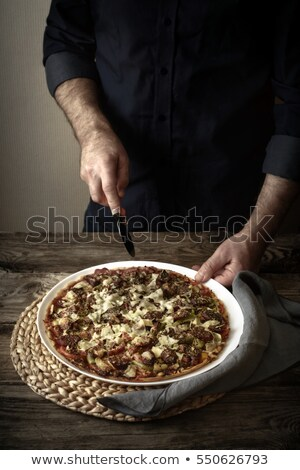 Stock photo: Man cuts the finished pizza on a white dish