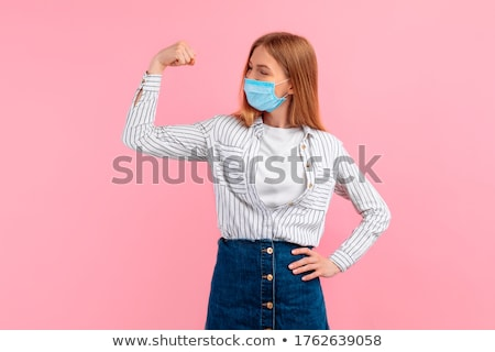 Young smiling woman in sports wear showing her biceps Stock photo © deandrobot