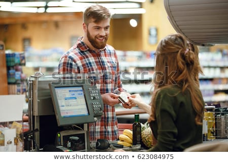 man standing near cashiers desk in supermarket shop stock photo © deandrobot