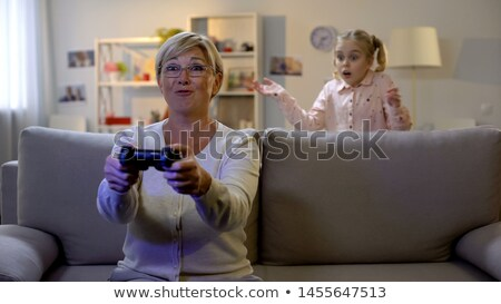 Grandmother and joystick. granny play video games. old woman on  Stock photo © popaukropa